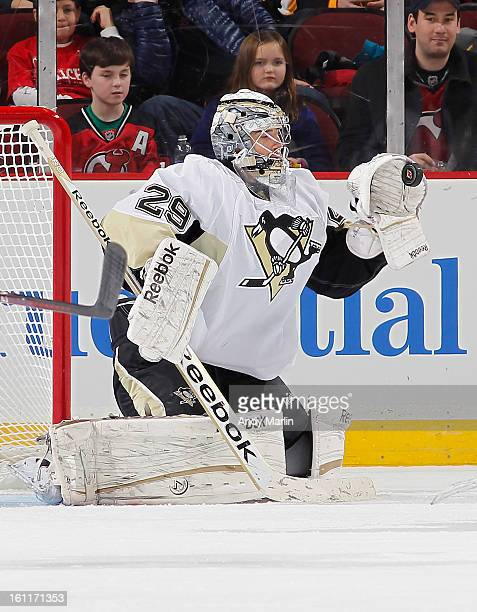 MarcAndre Fleury of the Pittsburgh Penguins makes a glove save against the New Jersey Devils during the game at the Prudential Center on February 9...