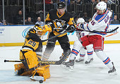 MarcAndre Fleury of the Pittsburgh Penguins makes a save as Tanner Glass of the New York Rangers and Christian Ehrhoff of the Pittsburgh Penguins...
