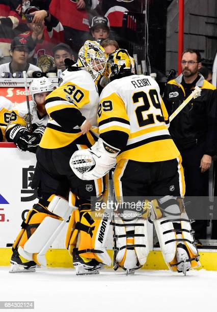 MarcAndre Fleury of the Pittsburgh Penguins skates to the bench as he talks to his replacement Matt Murray of the Pittsburgh Penguins after giving up...