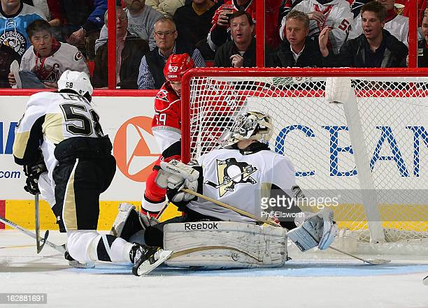 MarcAndre Fleury of the Pittsburgh Penguins slides across the crease to block a wraparound chance by Chad LaRose of the Carolina Hurricanes of the...