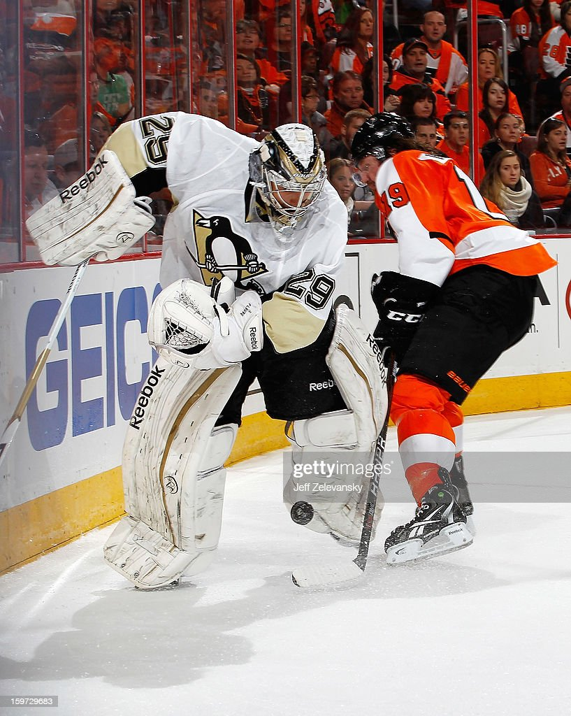 Marc-Andre Fleury #29 of the Pittsburgh Penguins tries to clear the puck in front of Scott Hartnell #19 of the Philadelphia Flyers at Wells Fargo Center on January 19, 2013 in Philadelphia, Pennsylvania.