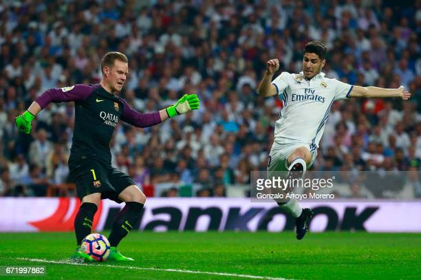 MarcAndre ter Stegen of Barcelona clears the ball under pressure from Marco Asensio of Real Madrid during the La Liga match between Real Madrid CF...