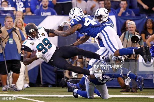 Marcedes Lewis of the Jacksonville Jaguars is tackled by Rashaan Melvin and Antonio Morrison of the Indianapolis Colts after a reception during the...