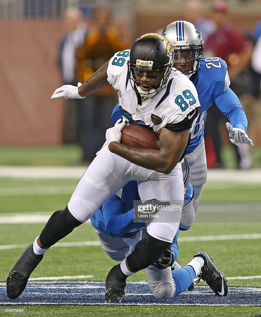 Marcedes Lewis #89 of the Jacksonville Jaguars runs for a short gain as Don Carey #26 of the Detroit Lions gives chase during the preseason game at Ford Field on August 22, 2014 in Detroit, Michigan. The Lions defeated the Jaguars 13-12.
