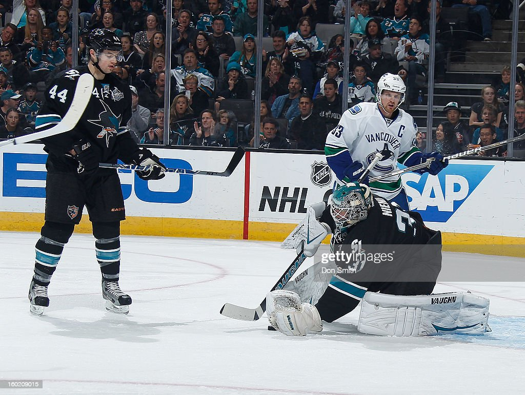 Marc-Edouard Vlasic #44 and Antti Niemi #31 of the San Jose Sharks protect the net against Henrik Sedin #33 of the Vancouver Canucks during an NHL game on January 27, 2013 at HP Pavilion in San Jose, California.
