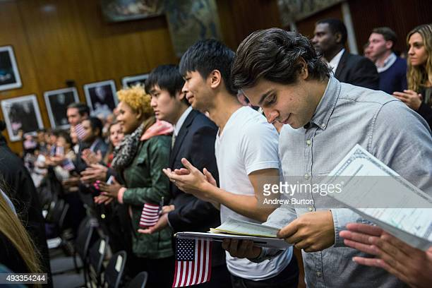 Marcel Andrade Yunes a new US citizen looks at his certficate of citizenship at the end of his naturalization ceremony at the United States District...