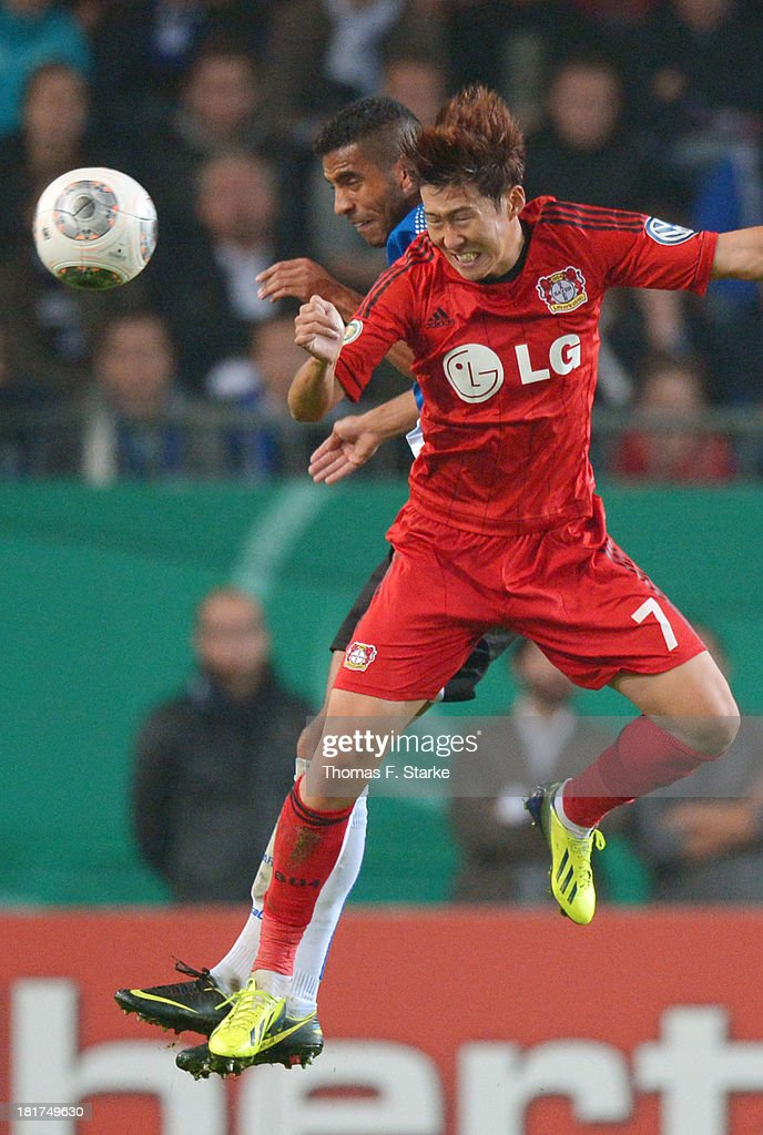 Marcel Appiah (L) of Bielefeld and Heung - Min Son of Leverkusen head for the ball during the DFB Cup match between Arminia Bielefeld and Bayer 04 Leverkusen at Schueco Arena on September 24, 2013 in Bielefeld, Germany.