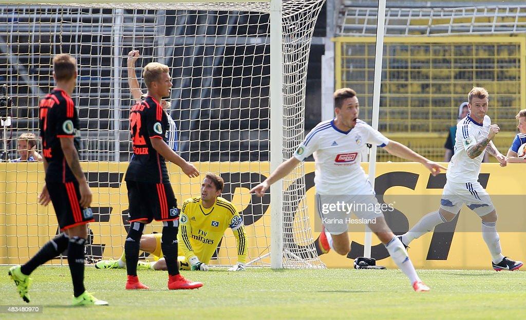 Marcel Baer and Rene Klingbeil of Jena celebrate the opening goal by Justin Gerlach Goalkeeper Rene Adler of Hamburger SV looks dejected during the...