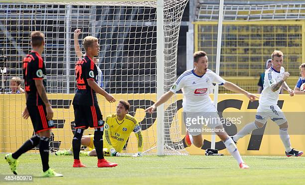 Marcel Baer and Rene Klingbeil of Jena celebrate the opening goal by Justin Gerlach Goalkeeper Rene Adler of Hamburger SV looks dejected during the...