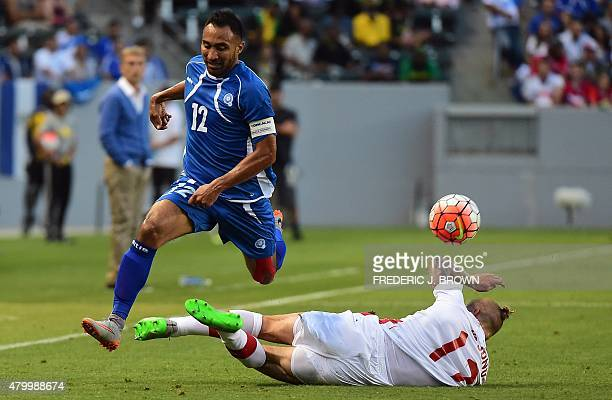 Marcel De Jong of Canada slides into a tackle evaded by Arturo Alvarez of El Salvador during their 2015 Concacaf Gold Cup match in Carson California...