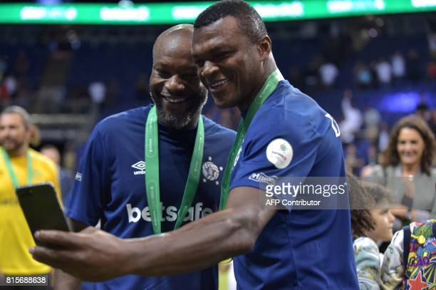 Marcel Desailly and William Gallas take a photograph as France celebrate their victory after the Star Sixes final football match between France and...