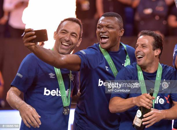 Marcel Desailly takes a photograph with Youri Djorkaeff and and Ludovic Giuly as France celebrate their victory after the Star Sixes final football...