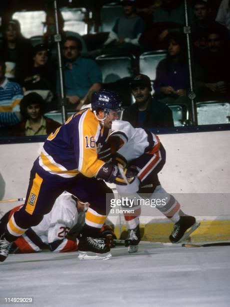 Marcel Dionne of the Los Angeles Kings skates on the ice as a defender from the New York Islanders checks him during their game on December 9 1986 at...