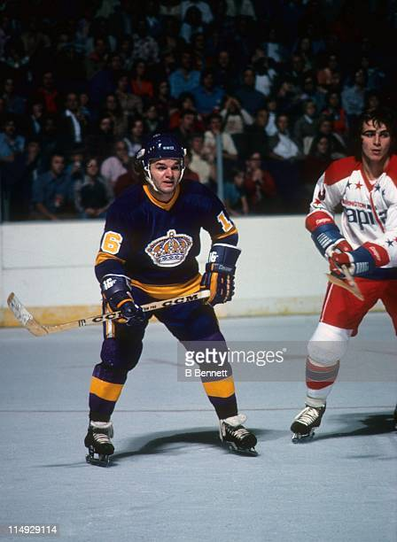 Marcel Dionne of the Los Angeles Kings skates on the ice while being defended by Peter Scamurra of the Washington Capitals during their game on...