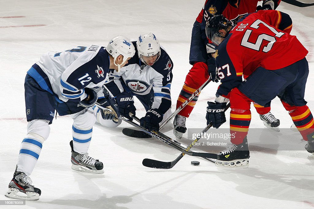 Marcel Goc #57 of the Florida Panthers crosses sticks with Evander Kane #9 of the Winnipeg Jets and teammate Olli Jokinen #12 at the BB&T Center on January 31, 2013 in Sunrise, Florida.