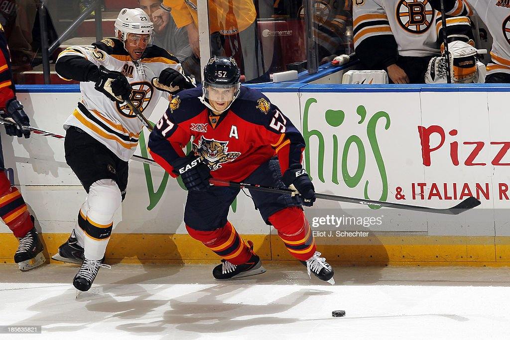 Marcel Goc of the Florida Panthers skates for the puck against Chris Kelly of the Boston Bruins at the BBT Center on October 17 2013 in Sunrise...