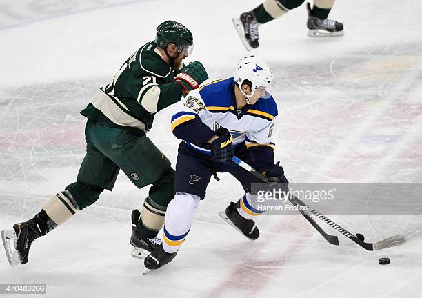 Marcel Goc of the St Louis Blues controls the puck against Kyle Brodziak of the Minnesota Wild during the first period in Game Three of the Western...