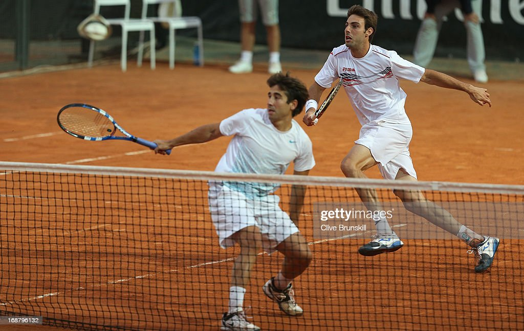 Marcel Granollers and <a gi-track='captionPersonalityLinkClicked' href=/galleries/search?phrase=Marc+Lopez&family=editorial&specificpeople=2564593 ng-click='$event.stopPropagation()'>Marc Lopez</a> of Spain in action against Nenad Zimonjic of Serbia and Julien Benneteau of France in their first round match during day four of the Internazionali BNL d'Italia 2013 at the Foro Italico Tennis Centre on May 15, 2013 in Rome, Italy.