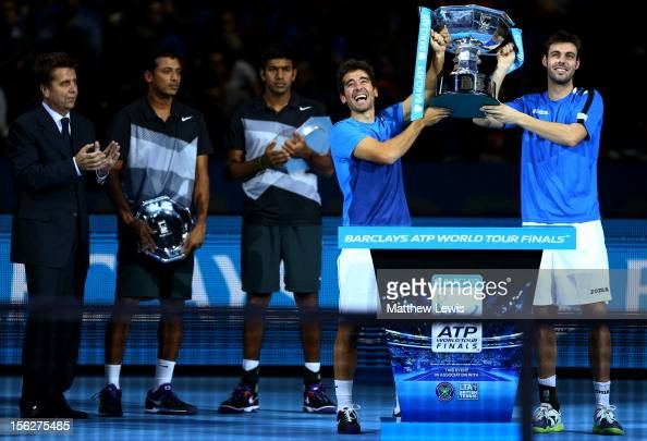Marcel Granollers of Spain and Marc Lopez of Spain pose with the trophy next to Rohan Bopanna of India Mahesh Bhupathi of India and Brad Drewett...