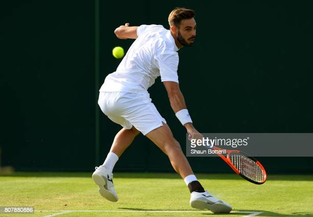 Marcel Granollers of Spain plays a backhand during the Gentlemen's Singles first round match against Dudi Sela on day two of the Wimbledon Lawn...