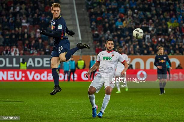Marcel Halstenberg of Leipzig and Raul Bobadilla of Augsburg battle for the ball during the Bundesliga match between FC Augsburg and RB Leipzig at...