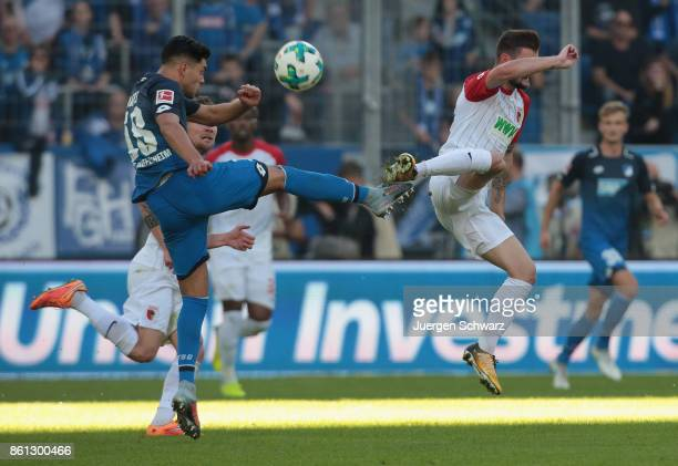 Marcel Heller of Augsburg and Nadiem Amiri of Hoffenheim fight for the ball during the Bundesliga match between TSG 1899 Hoffenheim and FC Augsburg...