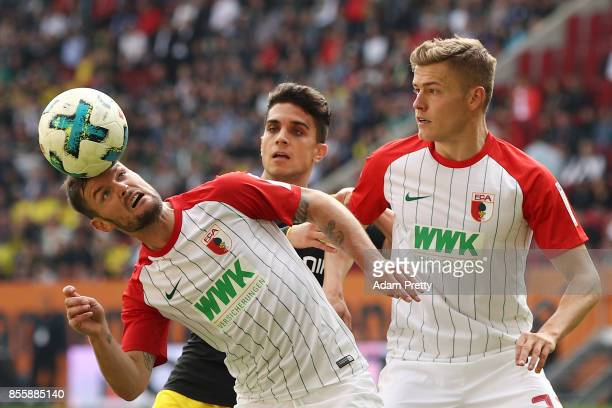 Marcel Heller of Augsburg Christian Pulisic of Dortmund and Alfred Finnbogason of Augsburg during the Bundesliga match between FC Augsburg and...