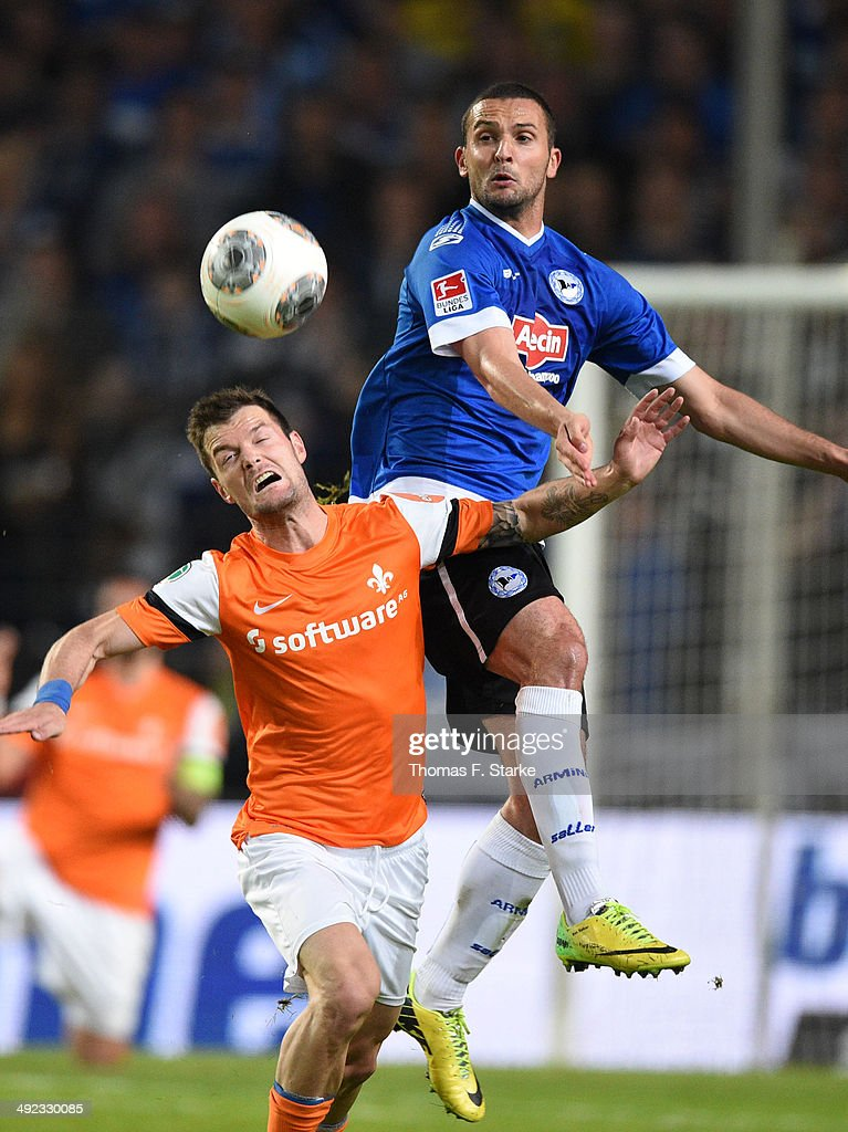 Marcel Heller (L) of Darmstadt and Ben Sahar of Bielefeld head for the ball during the Second Bundesliga Playoff Second Leg match between Arminia Bielefeld and Darmstadt 98 at Schueco Arena on May 19, 2014 in Bielefeld, Germany.
