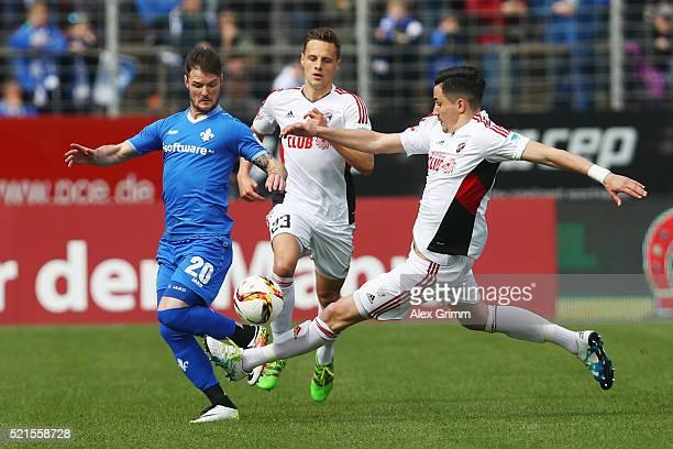 Marcel Heller of Darmstadt is challenged by Benjamin Huebner of Ingolstadt during the Bundesliga match between SV Darmstadt 98 and FC Ingolstadt at...