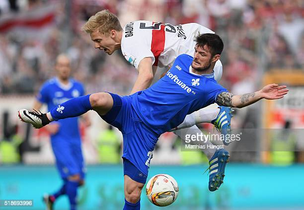 Marcel Heller of Darmstadt is challenged by Timo Baumgartl of Stuttgart during the Bundesliga match between SV Darmstadt and VfB Stuttgart at...