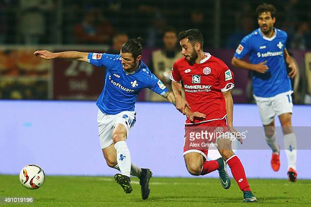 Marcel Heller of Darmstadt is challenged by Yunus Malli of Mainz during the Bundesliga match between SV Darmstadt 98 and 1FSV Mainz 05 at...