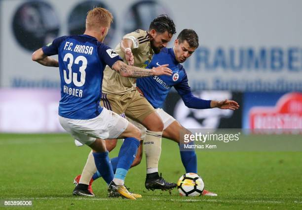 Marcel Hilssner Marcos Alvarez and Julian Riedel battle for the ball during the third league match between FC Hansa Rostock and VfL Osnabrueck at...