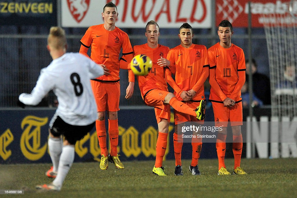 Marcel Hilssner of Germany (L) fires in a free kick towards the Netherlands wall during the U18 International Friendly match between The Netherlands and Germany on March 26, 2013 in Vriezenveen, Netherlands.