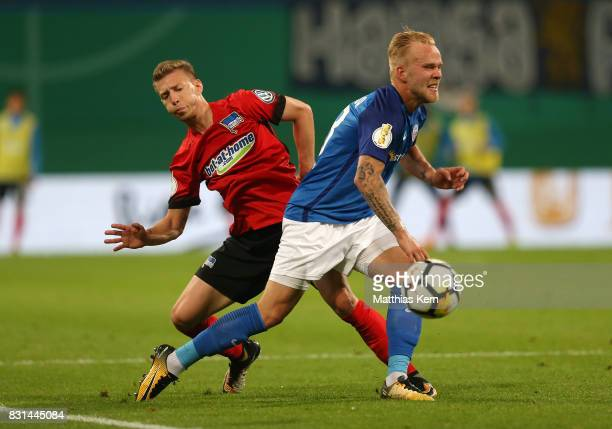 Marcel Hilssner of Rostock battles for the ball with Mitchell Weiser of Berlin during the DFB Cup first round match between FC Hansa Rostock and...