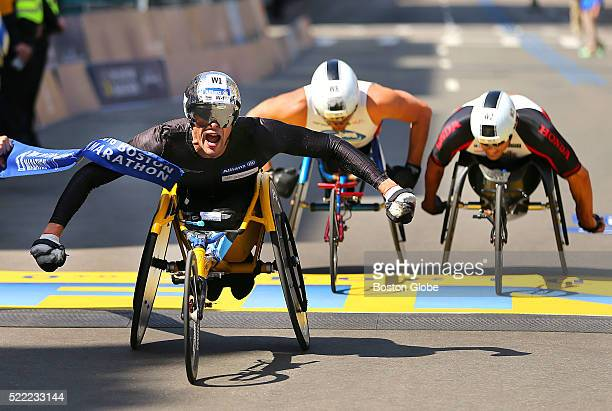 Marcel Hug of Switzerland crosses the finish line to win the mens wheelchair division in a close finish with Ernst Van Dyk and Kurt Feanley during...