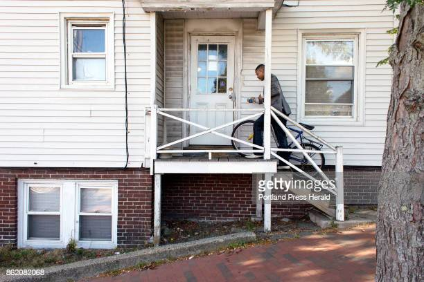 Marcel Kabongo Mafuku an asylee from the Congo carries his bike into the Parkside apartment building where he lives with a roommate The bicycle is...