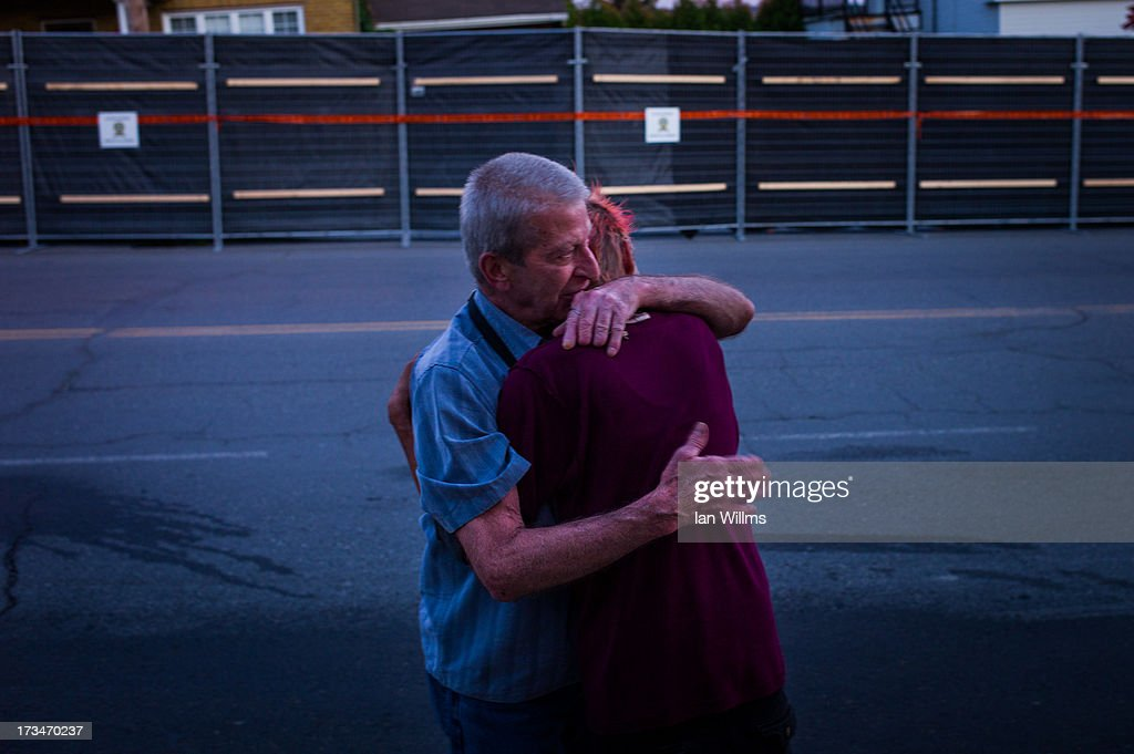 Marcel Larrivee (L) comforts Patricia Landry after the pair first witnessed the aftermath of the destruction on July 14, 2013 in Lac-Megantic, Quebec, Canada. A train derailed and exploded into a massive fire that flattened dozens of buildings in the town's historic district, leaving 60 people dead or missing in the early morning hours of July 6.