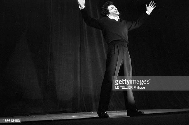 Marcel Mouloudji On Stage Portrait de Marcel MOULOUDJI chantant sur une scène les bras écartés en l'air
