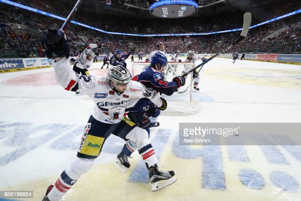 Marcel Noebels of Berlin is challenged by Garrett Festerling of Mannheim during the DEL Playoffs quarter finals Game 7 between Adler Mannheim and...