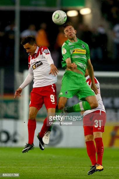 Marcel Platzek of Essen and Christoph Kramer of Mnchengladbach go up for a header during the DFB Cup first round match between RotWeiss Essen and...
