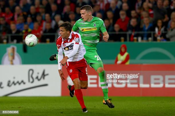Marcel Platzek of Essen and Matthias Ginter of Mnchengladbach go up for a header during the DFB Cup first round match between RotWeiss Essen and...