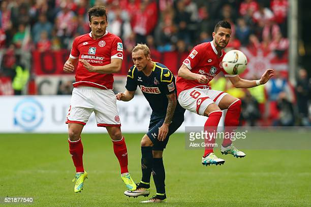 Marcel Risse of Koeln is challenged by Giulio Donati and Danny Latza of Mainz during the Bundesliga match between 1 FSV Mainz 05 and 1 FC Koeln at...
