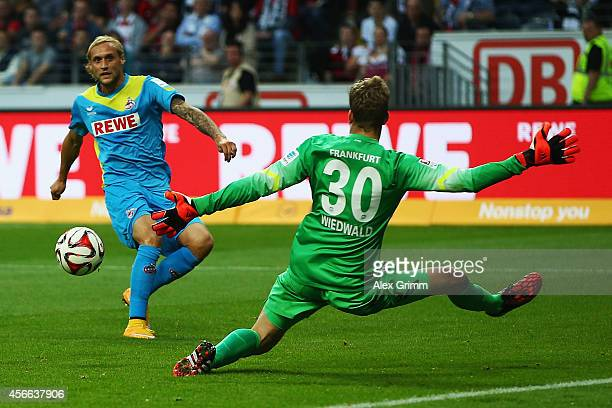 Marcel Risse of Koeln scores his team's first goal against goalkeeper Felix Wiedwald of Frankfurt during the Bundesliga match between Eintracht...