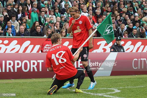 Marcel Risse of Mainz celebrates with his team mate Lewis Holtby after scoring his team's first goal during the Bundesliga match between Werder...
