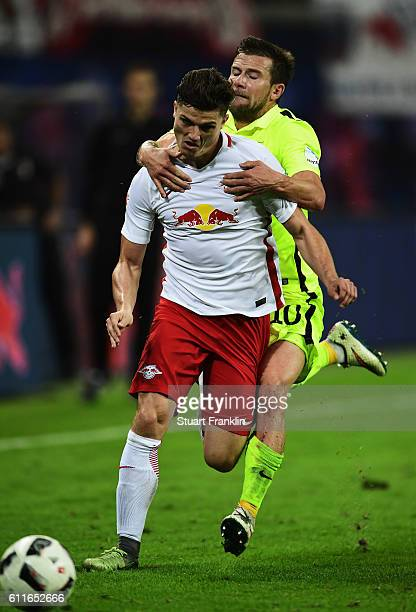 Marcel Sabitzer of Leipzig is challenged by Daniel Baier of Augsburg during the Bundesliga match between RB Leipzig and FC Augsburg at Red Bull Arena...