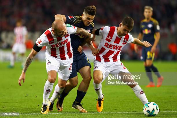 Marcel Sabitzer of RB Leipzig battles for the ball with Konstantin Rausch and Salih Ozcan of FC Koeln during the Bundesliga match between 1 FC Koeln...