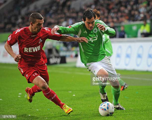 Marcel Schaefer of Wolfsburg is challenged by Lukas Podolski of Koeln during the Bundesliga match between VfL Wolfsburg and 1 FC Koeln at Volkswagen...