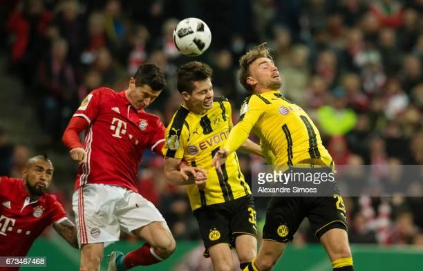 Marcel Schmelzer and Julian Weigl of Borussia Dortmund challenge Robert Lewandowski of FC Bayern Muenchen during the DFB Cup Semi Final match between...