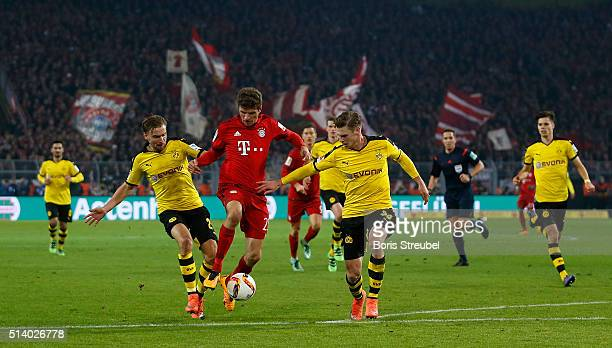 Marcel Schmelzer and Lukasz Piszczek of Borussia Dortmund challenge Thomas Mueller of Bayern Munich during the Bundesliga match between Borussia...