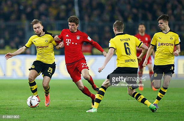 Marcel Schmelzer of Borussia Dortmund and Thomas Mueller of Bayern Munich compete for the ball during the Bundesliga match between Borussia Dortmund...